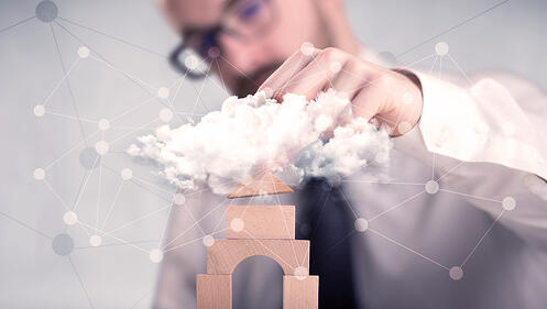 Young handsome businessman using wooden building blocks behind cloud concept